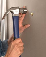 hammering-a-picture-frame-wall-hook-into-a-wall